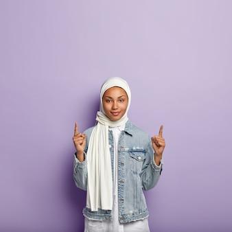 Plan vertical d'une femme musulmane confiante à la peau sombre, pointe vers le haut, montre un grand espace de copie vers le haut pour les clients, porte une écharpe en soie blanche et un manteau en jean, isolé sur un mur violet