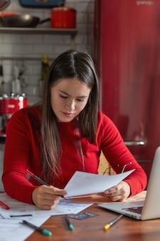 Plan vertical d'une femme sérieuse aux taches de rousseur, l'architecte détient un document, un crayon, s'assoit à une table de cuisine en bois, étudie un contrat, prépare un projet futur, analyse des documents. concept de personnes, de travail, de carrière et d'emploi