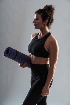 Plan vertical d'une femme sportive en vêtements de sport portant un karemat roulé se préparant à l'entraînement sur fond de mur blanc. concept de mode de vie sportif