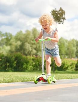 Plan vertical d'une heureuse petite fille riant joyeusement tout en faisant du kick-scooter dans le parc sur une journée chaude et ensoleillée copyspace émotions expressif enfants enfants concept de bonheur.