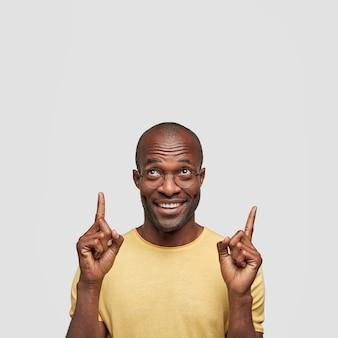 Plan vertical d'un homme d'âge moyen satisfait pointe vers le haut