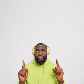 Plan vertical d'un homme barbu mécontent à la peau foncée pointe des index au-dessus du mécontentement qui porte des écouteurs sans fil sur les oreilles un sweat à capuche décontracté pose contre un mur blanc