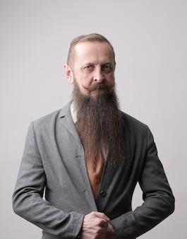 Plan vertical d'un homme avec une longue barbe et une moustache debout devant un mur gris