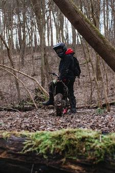 Plan vertical d'un motocycliste se prépare pour une balade dans une forêt
