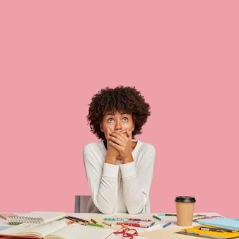 Plan vertical d'un multiplicateur professionnel à la peau sombre et choquée qui couvre la bouche des deux mains, porte un pull blanc, oublie la tâche importante, s'assoit à l'espace de copie du lieu de travail ci-dessus pour votre publicité