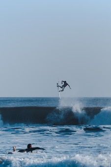 Plan vertical de surfeurs faisant des tours dans l'océan en prenant le dessus sur les vagues