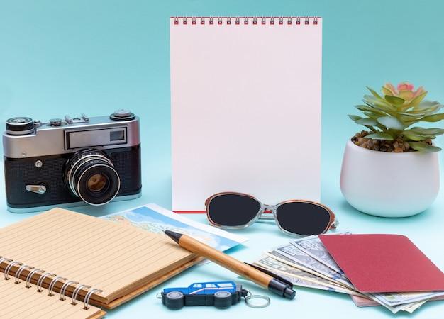 Plan de voyage, voyage de vacances, maquette touristique - lunettes, bloc-notes, stylo, appareil photo, argent, espèces, passeports et bloc-notes blanc vertical vierge pour votre lettrage. concept de voyage d'affaires. planification de voyage en ville