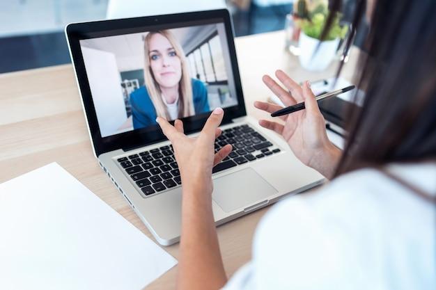Plan d'une vue arrière d'un médecin s'occupant d'une patiente par le biais d'un appel vidéo avec l'ordinateur portable à la maison.