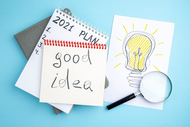Plan vue de dessus et bonne idée écrite sur des cahiers à spirale cahier gris lupa idée ampoule dessin sur papier sur fond bleu