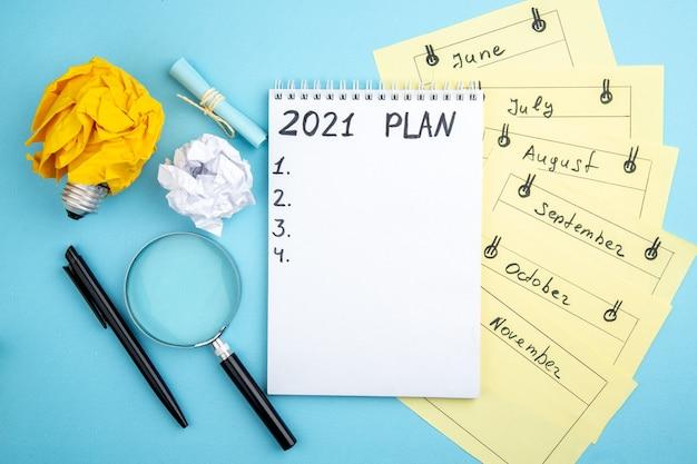 Plan vue de dessus écrit sur le bloc-notes cartes de rappel mensuel stylo lupa papier froissé avec concept d'ampoule idée sur fond bleu
