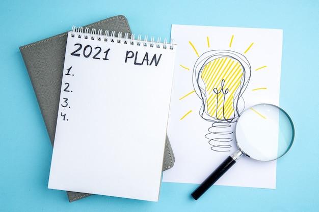 Plan vue de dessus écrit sur cahier à spirale cahier gris lupa idée ampoule dessin sur papier sur fond bleu