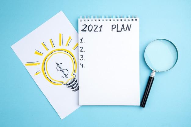 Plan vue de dessus écrit sur cahier à spirale lupa idée d'entreprise ampoule dessin sur papier sur fond bleu