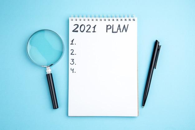 Plan vue de dessus écrit sur cahier à spirale stylo lupa sur fond bleu