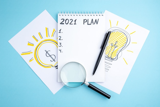 Plan Vue De Dessus écrit Sur Cahier à Spirale Stylo Lupa Idée Ampoules Dessin Sur Papiers Sur Fond Bleu Photo Premium