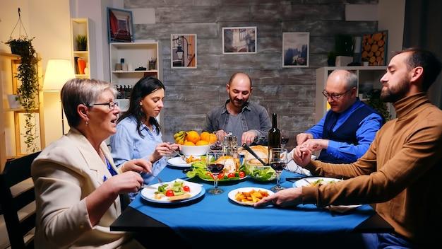 Plan de zoom arrière d'un frère servant sa sœur avec des pommes de terre lors d'un dîner en famille.