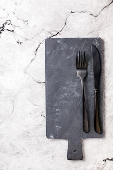 Planche d'ardoise noire pour alimenter une fourchette et un couteau.