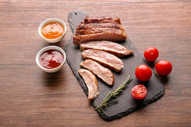 Planche d'ardoise avec de savoureux steak grillé, tomates fraîches et sauces sur table en bois
