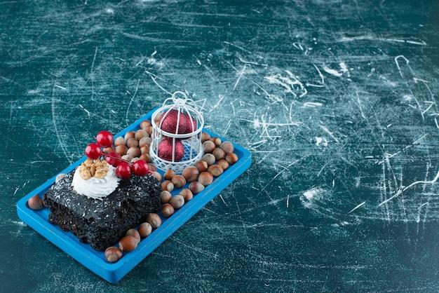 Une planche bleue avec un morceau de gâteau au chocolat et des noix de macadamia. photo de haute qualité