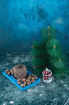 Une planche bleue avec une tarte au chocolat et des noix. photo de haute qualité