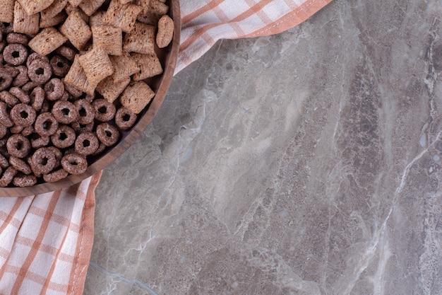 Une planche en bois avec des anneaux de céréales au chocolat sain et des flocons de maïs en pastilles de chocolat.