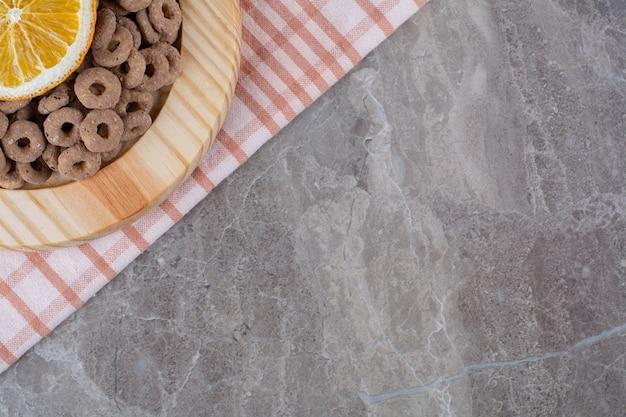 Une planche en bois d'anneaux de céréales au chocolat sain avec une tranche de fruit orange.