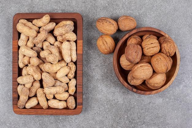Une planche de bois d'arachides et de noix saines en coque