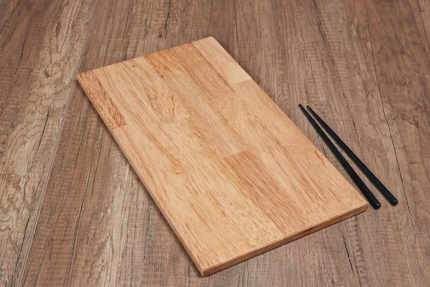 Planche de bois et baguettes sur plancher en bois