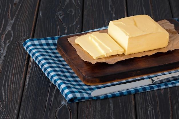 Planche de bois avec beurre sur serviette à carreaux bleu