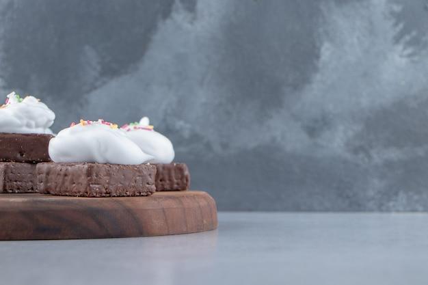Une planche en bois de biscuit au chocolat avec des pépites colorées et de la crème. photo de haute qualité