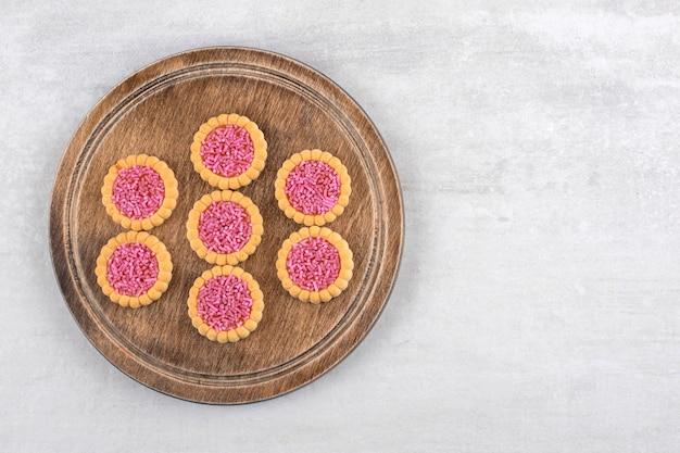 Une planche en bois de biscuits sucrés avec des paillettes dans le trou sur un fond de pierre.