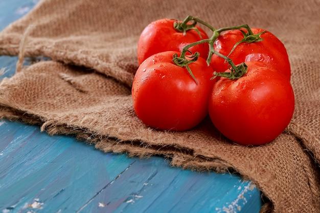 Planche de bois bleu photo horizontale de la branche de tomates juteuses rouge.