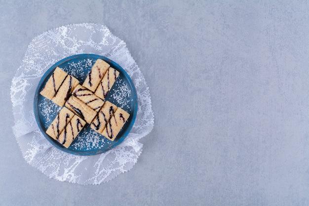 Une planche en bois bleue de bâtonnets sucrés avec des pépites et du sirop de chocolat
