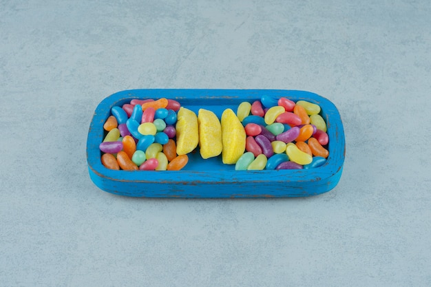 Une planche en bois bleue de bonbons à mâcher en forme de banane avec des bonbons aux haricots colorés