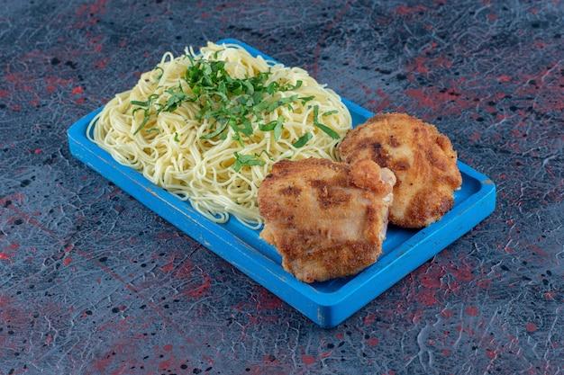 Une planche en bois bleue de nouilles et d'escalopes de poulet.