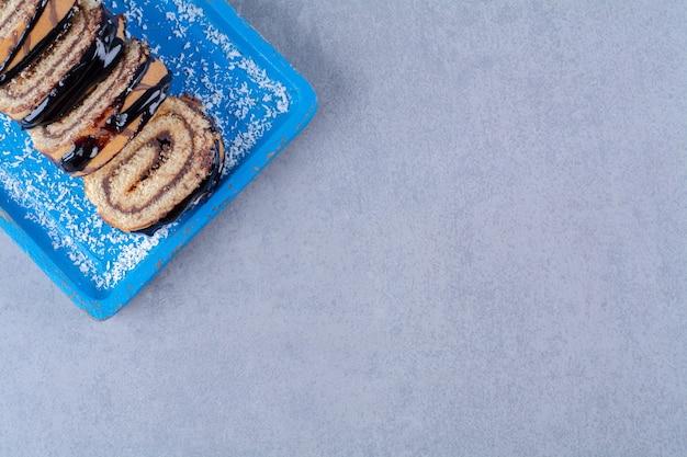 Une planche en bois bleue de pain sucré en tranches avec du sirop de chocolat.