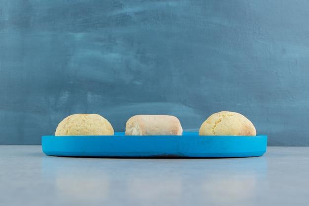 Une planche en bois bleue pleine de biscuits sucrés.