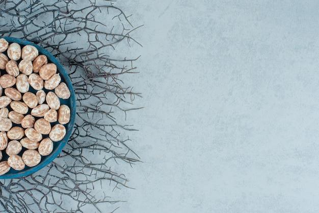 Une planche de bois bleue pleine de délicieux pain d'épice sucré sur une surface blanche