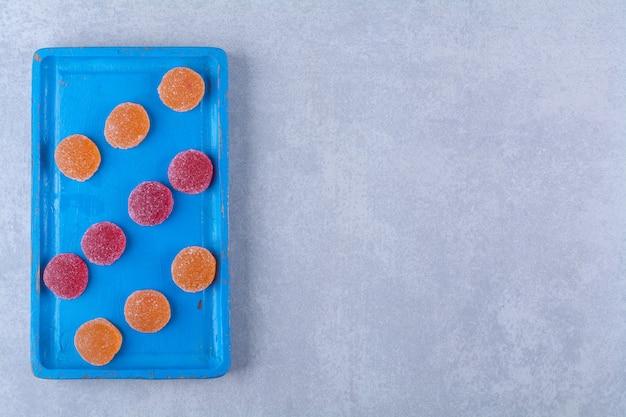 Une planche en bois bleue pleine de marmelades sucrées rouges et oranges.