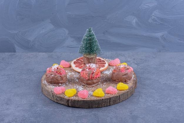 Une planche de bois avec des bonbons et des biscuits à la gelée sucrée