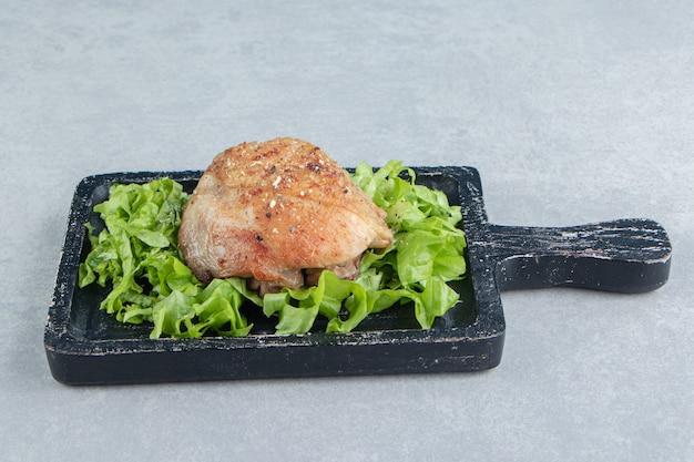 Une planche de bois avec des cuisses de poulet frites et une salade de laitue.