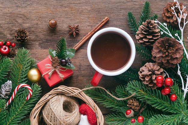Planche de bois décorer avec des feuilles de pin, des pommes de pin, des boules de houx, des cannes de bonbon et une tasse de chocolat rouge dans le concept de noël