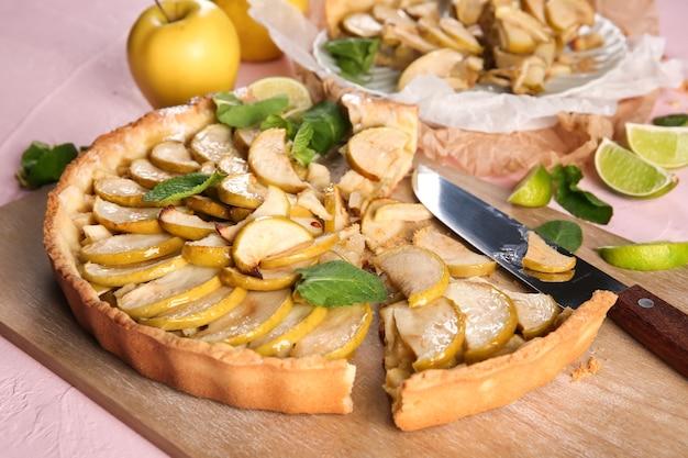 Planche de bois avec une délicieuse tarte aux pommes maison sur table