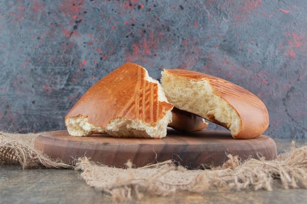 Une planche en bois de délicieuses pâtisseries sucrées sur un sac