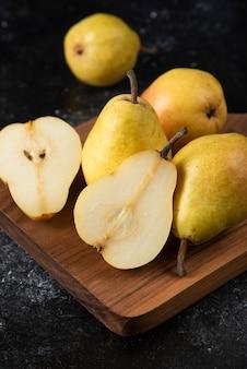 Planche de bois de délicieuses poires jaunes sur une surface noire.