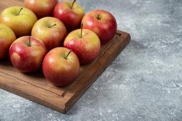 Planche de bois de délicieuses pommes fraîches sur une surface en marbre.
