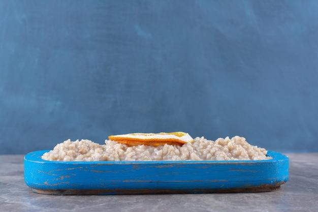 Une planche en bois avec de délicieux flocons d'avoine et une tranche de fruit orange.