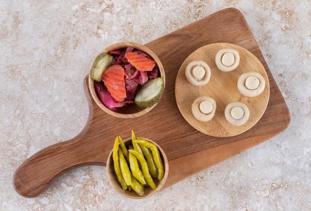 Une planche de bois de divers légumes sur une surface en marbre