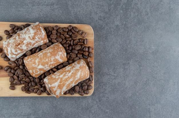Une planche de bois avec du pain d'épice sucré et des grains de café