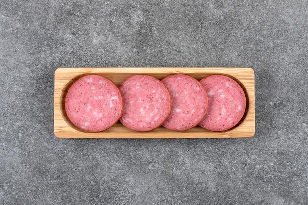 Planche de bois avec du salami en tranches placé sur une table en pierre.