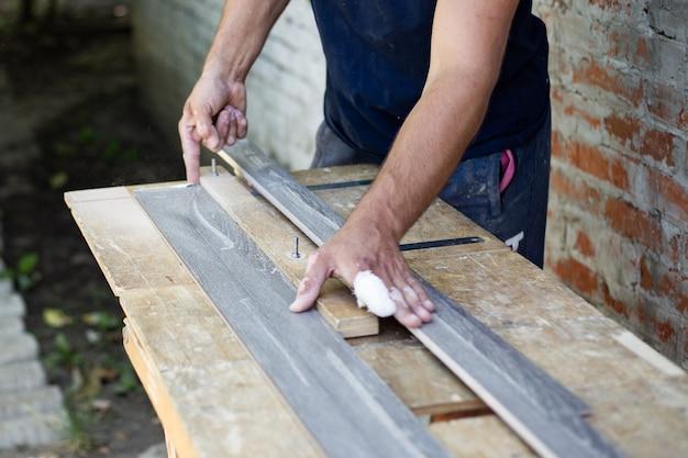 La planche de bois est sciée dans le sens de la longueur sur la machine. travaux de menuiserie.